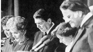 U.S. President Ronald Reagan, along with others, bow their heads and pray during the National Prayer Breakfast, at a Washington hotel, Thursday, Feb. 5, 1987. From left are, Transportation Secretary Elizabeth Dole, first lady Nancy Reagan, the President, Marcia Coats, wife of Rep. Daniel Coats of Indiana, and Rev. Billy Graham. During the breakfast, the president joined in a silent prayer for American hostages in Lebanon and missing church of England envoy Terry Waite. (AP Photo/J. Scott Applewhite)