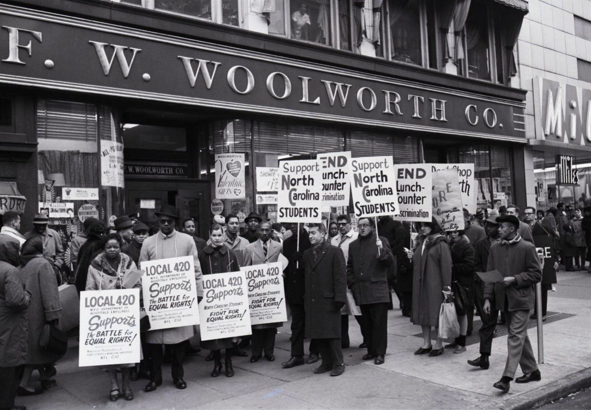 """(Original Caption) Feb. 13, 1960 — New York, NY: Placard-carrying demonstrators mass in front of a Woolworth store in Harlem here Feb. 13 to protest lunch counter discrimination practiced in Woolworth stores in Greensboro, Charlotte and Durham, NC. The demonstrators, who belong to an organization known as """"CORE"""" (Congress of Racial Equality), are urging Harlem residents not to patronize Woolworth stores until discrimination ends in the stores in the three Southern cities."""