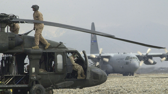 A U.S. C-130 cargo plane prepares for takeoff in front of a UH-60 Blackhawk helicopter at the U.S. military air base in Bagram, Afghanistan on Thursday Jan. 30, 2003. U.S. forces in southeastern Afghanistan fought their largest-scale battle in nearly a year this week against a contingent of rebel fighters. The military says the attacks and fire fights show that the war in Afghanistan is still not over. (AP Photo/Aaron Favila)