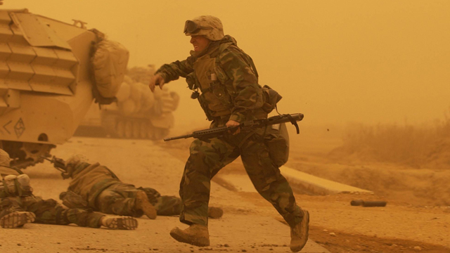 FILE - US Marines with 3rd Battalion, 7th Marines, 1st Marine Division, take cover after a mortar attack during a sandstorm on a road south of Baghdad, Iraq on Wednesday, March 26, 2003. (AP Photo/Laura Rauch, File)