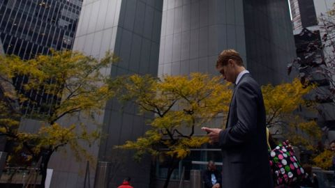 A man stands near Citigroup center building while working on his BlackBerry device. November 2008. (AP/Jin Lee)
