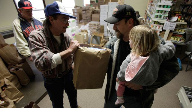 A man who had been laid off holds his daughter while taking free food from the weekly open food pantry at the Warren Family Mission in Warren, Ohio. March 2009 (AP /Amy Sancetta)