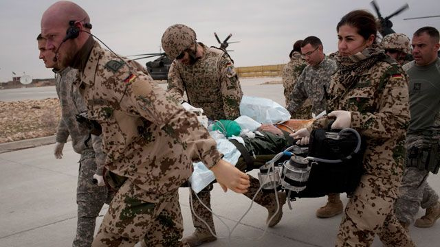 German and US Army soldiers rush with an injured German soldier to the German Army hospital in Kunduz, north of Kabul, Afghanistan. February 2011. (AP Photo/Anja Niedringhaus)