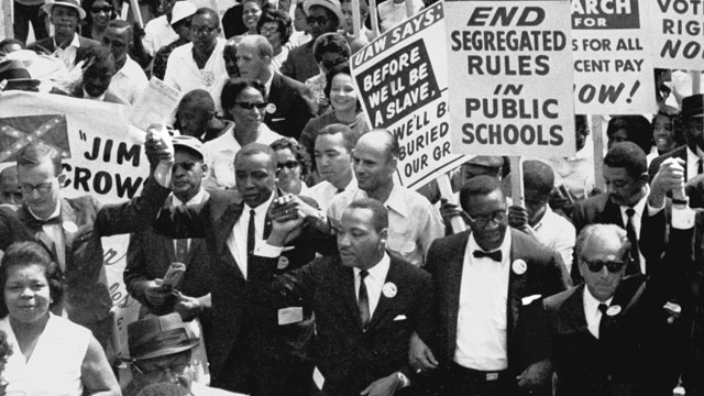 Dr. Martin Luther King Jr. marches in a line of men with arms linked during the March on Washington. August 1963. (AP Photo)