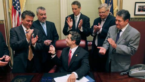 New York Gov. Andrew Cuomo hands pens to legislators after signing into law a bill legalizing same-sex marriage. June 2011. (AP/Mike Groll)