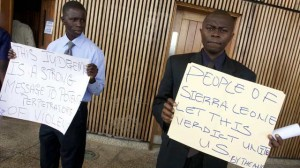 People hold signs outside the Special Court for Sierra Leone, where people gathered to watch a live broadcast of the verdict in the Netherlands-based trial of former Liberian president Charles Taylor, in Freetown, Sierra Leone Thursday, April 26, 2012.