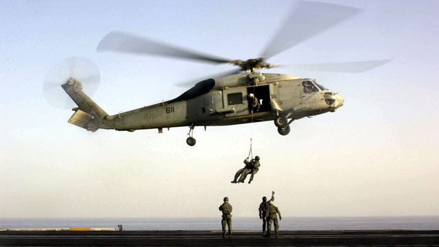 U.S. Navy Seals train with a SH-60F Seahawk helicopter on the flight deck of the USS Enterprise. October 2001. (AP Photo/U.S. Navy, Lance H. Mayhew Jr.)