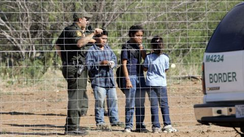 A Border Patrol agent stands on a ranch fence line with children taken into custody in South Texas brush country north of Laredo. June 2006. (AP /LM Otero)
