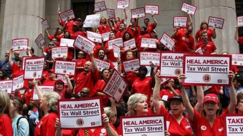 Nurses from the National Nurses United union protest for the Robin Hood Tax