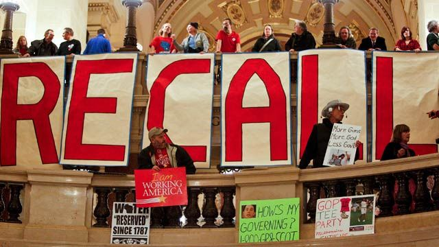 Protestors show off signs in the rotunda of the State Capitol prior to Gov. Scott Walker's state of the state address in Madison, Wis. January 2012. (AP Photo/Andy Manis)