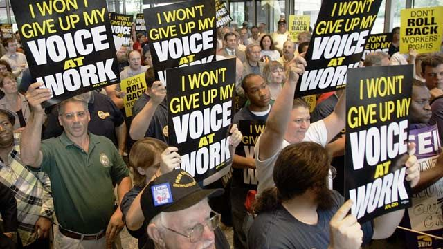 Supporters attending a labor rally hold signs supporting rights to unionize at United Steelworkers union headquarters in Pittsburgh, PA. July 2006. (AP Photo/Keith Srakocic)