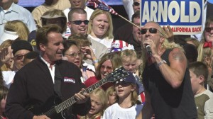 """Snyder (right) apparently was alright with Republican gubernatorial candidate Arnold Schwarzenegger, left, performing """"We Ain't Going to Take it Anymore,"""" during a campaign rally held at the Capitol in Sacramento, Calif.,  in 2003. (AP Photo/Rich Pedroncelli)"""