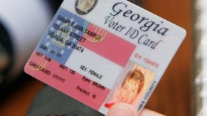 Sen. Bill Stephens, R-Canton, looks at a sample of a proposed new secure Voter ID. (AP Photo/Ric Feld)