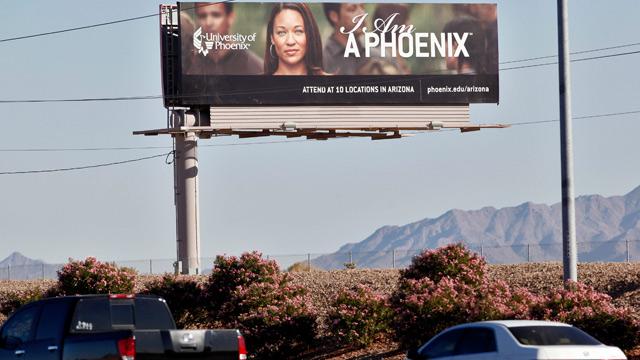 A University of Phoenix billboard is shown in Chandler, Arizona. (AP Photo/Matt York)