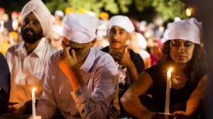 People cover their heads at a candle light vigil in Oak Creek, Wisconsin, Tuesday Aug. 7, 2012, for the victims of a mass shooting at the Sikh Temple of Wisconsin on Sunday. The vigil was held during the national night out event at the Oak Creek Civic Center. (Photo by Tom Lynn/AP)