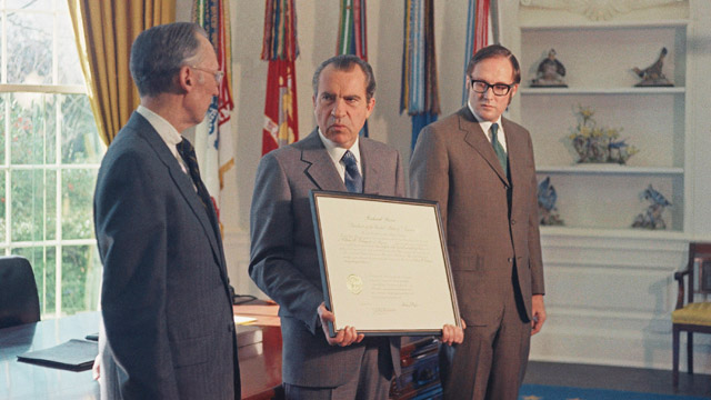 U.S. President Richard Nixon holds a commission that he will present to Lewis F. Powell Jr., left, and another will be given to William Rehnquist, right, at a White House ceremony in Washington, D.C., Wednesday, Dec. 22, 1971. Both Powell and Rehnquist are commissioned as Associate Justices of the Supreme Court and will take their oath Jan. 7, 1972. The two men were appointed to the Supreme Court by President Nixon. (AP Photo/Charles Tasnadi)