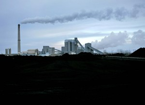 Sunflower Electric Cooperative's coal-fired power plant rises behind a 30-day-supply of coal in Holcomb, Kan. (AP Photo/Charlie Riedel)