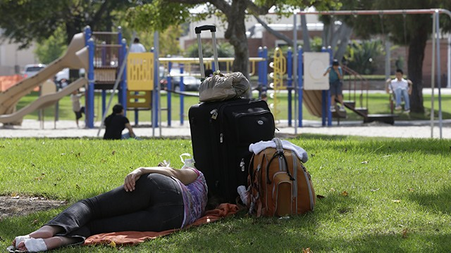 A homeless woman rests under a shade tree as children play at Lions park in Costa Mesa, Calif. October 2012. (AP Photo/Chris Carlson)