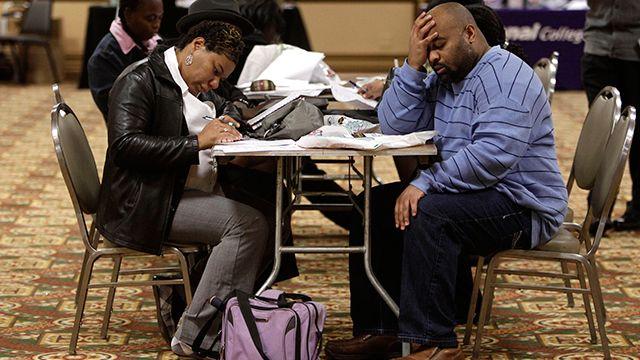 Tonya Crenshaw and Kendrick Haraalson fill out applications at a job fair in Brookpark, Ohio. (AP Photo/Tony Dejak)