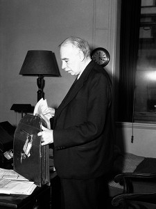 Lord John Maynard Keynes, brilliant financial expert and adviser to the Treasury will accompany Lord Halifax when he returns to Washington for consultations in connection with the ending of Lend-Lease. Lord Keynes in his office at the Treasury, in London, on Aug. 24, 1945, packing documents into his portfolio, in preparation for his journey. (AP Photo)
