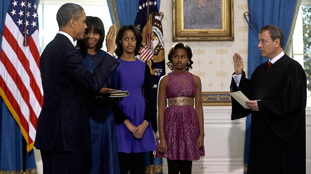 President Barack Obama is officially sworn-in by Chief Justice John Roberts in the Blue Room of the White House during the 57th Presidential Inauguration in Washington, Sunday Jan. 20, 2013. Next to Obama are first lady Michelle Obama, holding the Robinson Family Bible, and daughters Malia and Sasha. (AP Photo/Pool, Charles Dharapak)