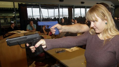 Clark Aposhian, President of Utah Shooting Sport Council, demonstrates with a plastic gun while Joanna Baginska, 4th grade teacher from Odyssey Charted School, in American Fork, uses a 40 cal. Sig Sauer during concealed-weapons training for the teachers. Dec. 27, 2012, in West Valley City, Utah. (AP Photo/Rick Bowmer)