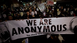 Anonymous supporters wearing Guy Fawkes masks pause for fellow protesters and members of the media to film and photograph them with a banner as they take part in a protest march along Whitehall to Britain's Houses of Parliament in London, Monday, Nov. 5, 2012. The protest was held on November 5, to coincide with the failed 1605 gunpowder plot to blow up the House of Lords. (AP Photo/Matt Dunham)