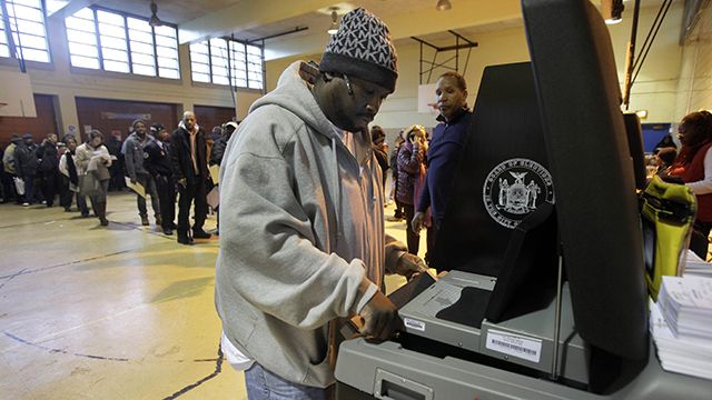 Poll worker Eric Carr, background center, watches a technician for the New York City Board of Elections clear a paper jam in a ballot scanner as voters wait to scan their ballots, at a school in New York's Harlem neighborhood, Nov. 6, 2012. (AP Photo/Richard Drew)