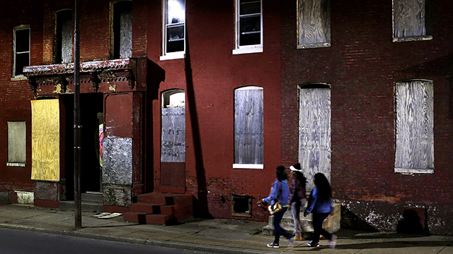 In this March 29, 2013 photo, women walk past blighted row houses in Baltimore. Baltimore is far from the worst American city for poverty, but it faces all the problems of cities where vast numbers of the poor now live. The US Census Bureau puts the number of Americans in poverty at levels not seen since the mid-1960s, while $85 billion in federal government spending cuts that began last month are expected to begin squeezing services for the poor nationwide. (AP Photo/Patrick Semansky)