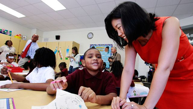 Michelle Rhee, right, talks to third grader Kmone Feeling during a visit at J.O. Wilson Elementary School on Aug. 23, 2010 in Washington. D.C. Rhee was D.C.'s public schools chancellor at the time. Mayor Adrian Fenty, back second left, and school principal Sheryl Warley, left, stand at the back. (AP Photo/Manuel Balce Ceneta)