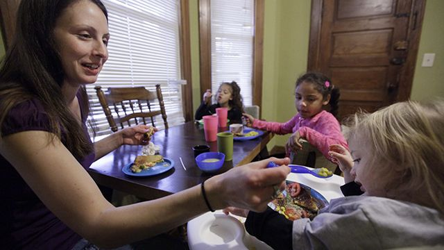 In this photo taken Nov. 23, 2009, Lisa Zilligen, 28, serves lunch to her three children, Miles, 20 months, Olivia 6, left, and Danielle, 8, in her home in Chicago. Zilligen, a single mother and full-time student at Loyola University has been getting food stamps for the past several months; sometimes the allotment runs out before the end of the month and the family ends up visiting a food pantry. (AP Photo/M. Spencer Green)