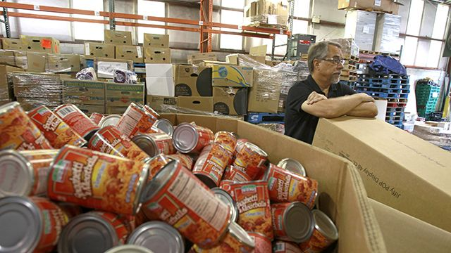 In this Monday, July 30, 2012 photo, Dave Krepcho, director of the Second Harvest Food Bank, looks over a supply of goods that have arrived at the food bank warehouse in Orlando, Fla. In the past four years, food distribution to 500 pantries, shelters, and other relief agencies in the six-county area has jumped about 60 percent. In the last year alone, that amounted to 36 million pounds of food. Krepcho estimates about 30 percent of those seeking help are first-timers. They're blue-collar and white-collar, many middle class, even some upper middle class. They include college-educated couples and professionals. (AP Photo/John Raoux)