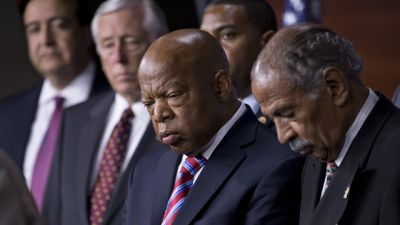Rep. John Lewis, D-Ga., center, and Rep. John Conyers, D-Mich., right, co-chairs of the Civil Rights Taskforce of the Congressional Black Caucus, join other members of the House to express disappointment in the Supreme Court's decision on Shelby County v. Holder that invalidates Section 4 of the Voting Rights Act, Tuesday, June 25, 2013, on Capitol Hill in Washington. Lewis, a prominent activist in the Civil Rights Movement in the 1960's, recalled being attacked and beaten trying to help people in Mississippi to register and vote in the 1960's. (AP Photo/J. Scott Applewhite)