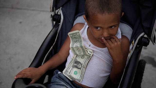 Four-year-old Nathan Hobbs, who lives in a homeless shelter with his mother, sits in a stroller with one-dollar bills he received for his birthday pinned to his chest in Los Angeles, Wednesday, September 14, 2011. (AP Photo/Jae C. Hong)
