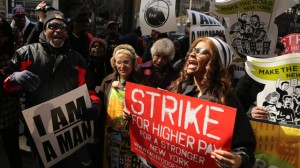 Demonstrators holds a sign and chant slogans outside of a Wendy's fast food restaurant, Thursday, April 4, 2013 in New York. (AP Photo/Mary Altaffer)
