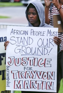 Beezy Dinkins, of St. Petersburg, Fla., demonstrates in front of the Seminole County Courthouse while the jury deliberates in the trial of George Zimmerman, Friday, July 12, 2013, in Sanford, Fla. Zimmerman has been charged with second-degree murder for the 2012 shooting death of Trayvon Martin. (AP Photo/John Raoux)