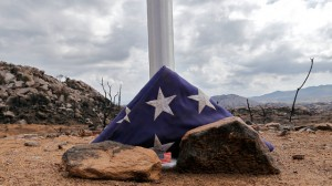 A flag sits at the base of a flag pole at the site where 19 firefighters died battling an Arizona wildfire on June 30th is shown Tuesday, July 23, 2013 in Yarnell, Ariz. As the fire grew out of control, the firefighters quickly worked to clear the area of scrub and brush hoping to endure the intense heat in their emergency shelters. (AP Photo/Matt York)
