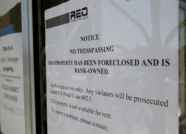 """A """"No Trespassing"""" sign is posted on a bank owned foreclosed home being offered for sale Tuesday, May 31, 2011, in Los Angeles. (AP Photo/Damian Dovarganes)"""