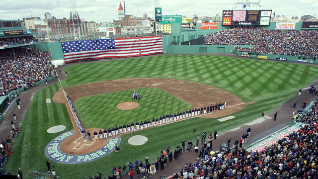 Members of the Boston Red Sox and Toronto Blue Jays line the field as a giant American flag is unveiled over the Green Monster wall before the game at Fenway Park in Boston, on opening day, Monday, April 1, 2002. (AP Photo/Victoria Arocho)