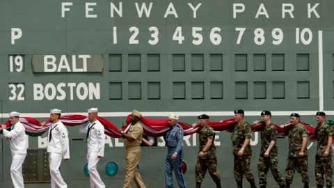 Veterans and members of the armed services carry an over-sized American flag past the scoreboard at Fenway Park in Boston following Memorial Day ceremonies prior to the Boston Red Sox game against the Baltimore Orioles Monday, May 31, 2004. (AP Photo/Winslow Townson)