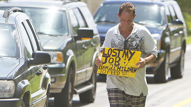 FILE - A man who did not wish to be identified, who lost his job two months ago after being hurt on the job, works to collect money for his family on a Miami street corner. (AP Photo/J Pat Carter, File)
