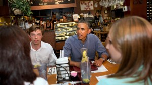 President Barack Obama talks with college students and their parents during a stop at Magnolia's Deli and Cafe in Rochester, New York on Aug. 22, 2013, on the first day of a two-day bus tour where he is expected to speak about college financial aid. (AP Photo/Jacquelyn Martin)