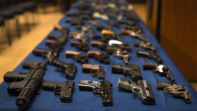 Nearly 100 confiscated illegal firearms rest on a table before a press conference with then-New York Mayor Michael Bloomberg. (AP Photo/John Minchillo)
