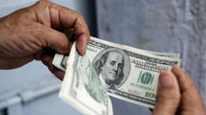 A man counts $100 bills. (AP Photo/Tsering Topgyal)