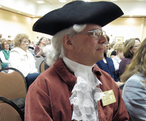 """Lynn Bergman, of Bismarck, N.D., listens to a speech at a """"tea party"""" rally of Republicans and conservatives at a Bismarck motel on Friday, Feb. 12, 2010. Bergman dressed as Revolutionary War author Thomas Paine for the occasion. (AP Photo/Dale Wetzel)"""