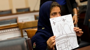 Nine-year-old Nabila Rehman holds a photo with a drawing she made depicting a drone strike that killed her grandmother, Tuesday, Oct. 29, 2013, during a news conference on Capitol Hill in Washington. (AP Photo/ Evan Vucci)