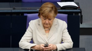 German Chancellor Angela Merkel uses her mobile phone at the German Federal Parliament Bundestag in Berlin, Germany. Merkel is among the world leaders who are trying to cope following allegations of massive electronic monitoring by the US National Security Agency in Berlin. (AP Photo/Markus Schreiber)