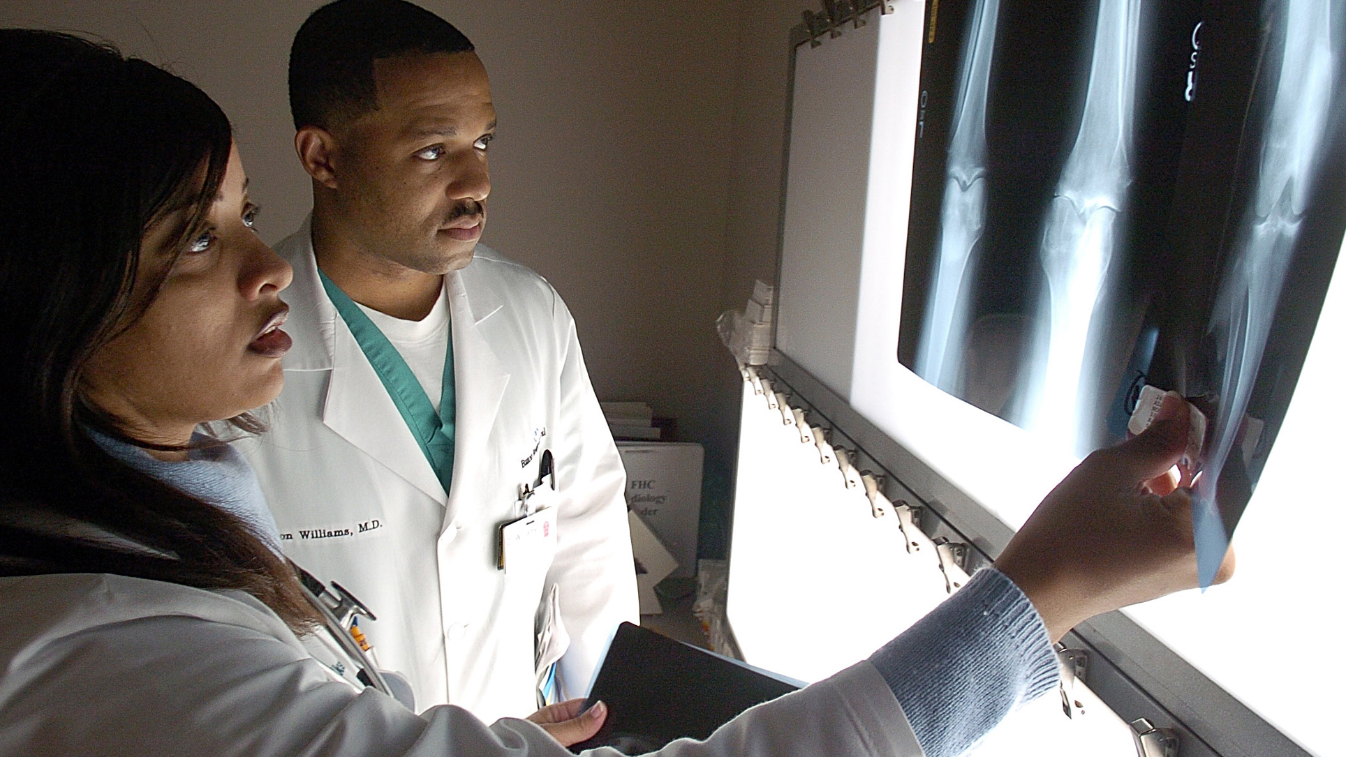"""** ADVANCE FOR Monday, DEC. 27 **Dr. Margeaux Coleman Walker, left, looks over x-rays with fellow resident Dr. Leon D. Williams at the clinic where they are doing their residencies in family medicine Dec. 9, 2004, in Baton Rouge, La. Tulane University is starting a new program to help reduce the shortage of doctors in rural Louisiana and is looking for students like Dr. Coleman Walker, who has known she wanted to be a doctor since she was 11 or 12 and helped her grandmother clean the doctor's office in Church Point, La., a town of 4,700. But she wants much more than a medical practice. """"Hopefully, when I want to retire, I'll be able to say, I worked hard and I made a difference in people's lives."""" (AP Photo/Bill Feig)"""
