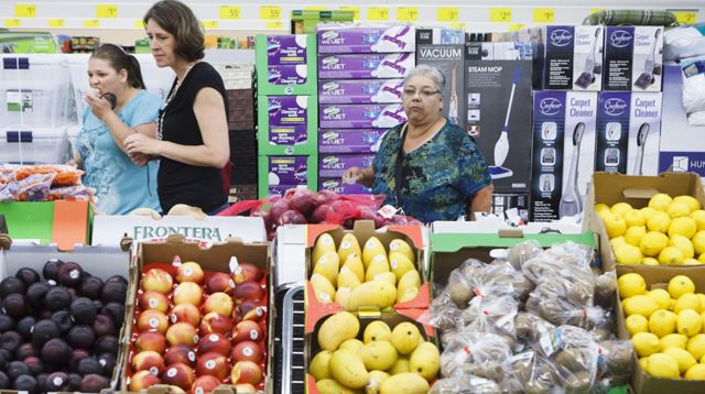 Customers check out prices of the high quality fresh produce in the store. (Michael Stravato/ AP Images for ALDI)