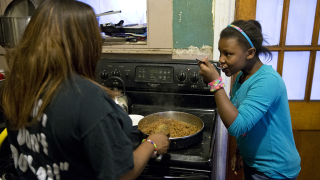 In this Tuesday, Oct. 8, 2013 photo, Jennifer Donald whose family receives money from the Supplemental Nutrition Assistance Program also know as food stamps, makes dinner with her daughter Jayla, 10, in Philadelphia. Families already buffeted by difficult economic times will see their food stamps benefits drop Nov. 1 as money allocated by the 2009 federal stimulus plan runs out. The average family of four will see benefits drop by $36 a month, a tough hit at a time when child poverty is climbing and Congress is debating a major cut to the Supplemental Nutrition Assistance Program. (AP Photo/Matt Rourke)